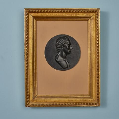 A round cast iron plaque with a portrait of Friedrich von Schiller -
