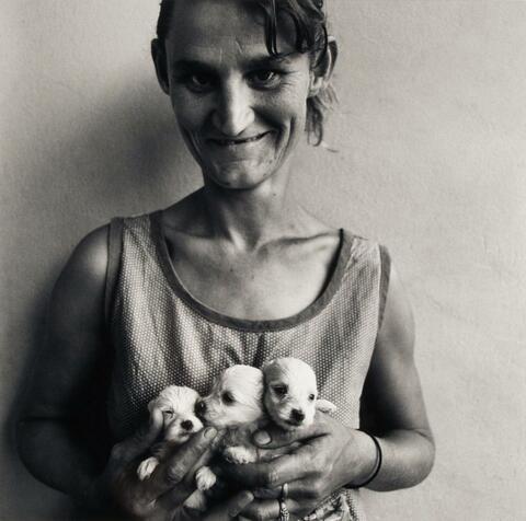 Roger Ballen - Wife of Abattoir worker holding three puppies, Orange Free State