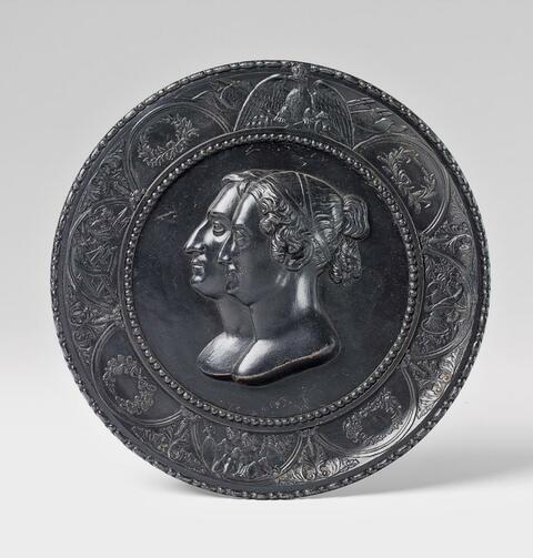 A black patinated cast iron tondo with a royal double portrait. -