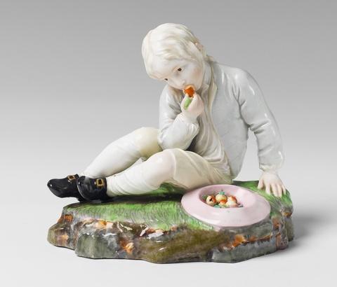 A Höchst porcelain figure of a boy eating a pear. -