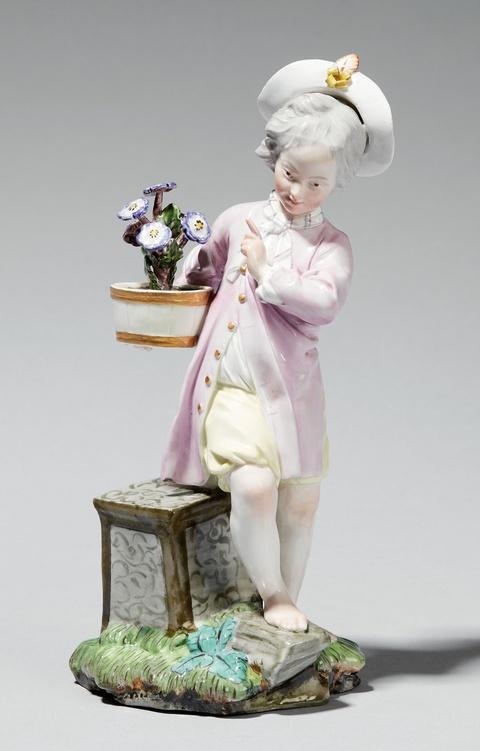 A Höchst porcelain figure of a boy with a shrub -
