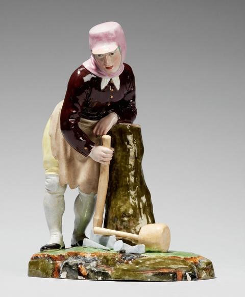 A Höchst porcelain figure of a collier splitting logs -
