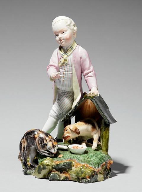 A Höchst porcelain model of a boy by a dog kennel -