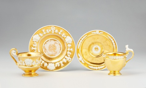 Two Vienna gilt porcelain cups with relief decor -