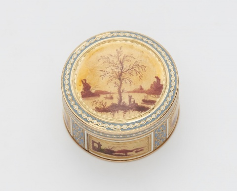 A small round enamelled gold snuff box -