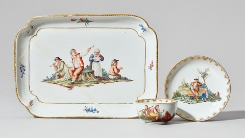 A Nymphenburg porcelain platter, cup, and saucer with peasant scenes -